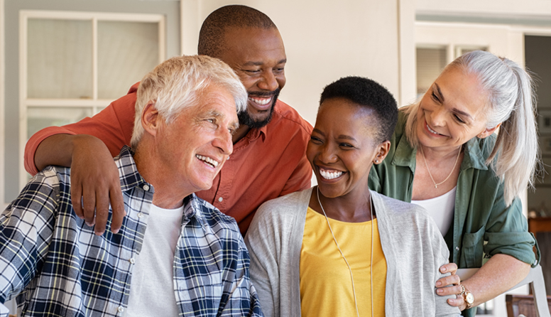 healthinsurance.com health insurance options that cover pre-existing conditions for retirees, group of four friends hugging and smiling at each other