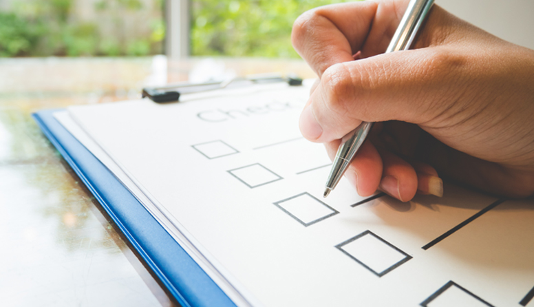 healthinsurance.com steps to prepare for your first telemedicine appointment, hand holding a pen checking off a checklist